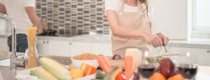 Unga lyckliga par som tillsammans hemma lagar mat i köket arkivbilder