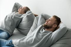 Unga lyckliga par som tillsammans kopplar av på den bekväma soffan på hom arkivbild