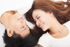Unga lyckliga par som tillsammans ligger Arkivbilder