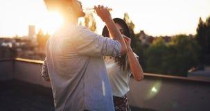 Unga lyckliga par som utomhus rostar med öl Arkivfoton