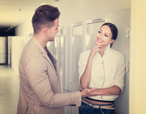 Unga lyckliga par som väljer det nya kylskåpet i stormarknad Royaltyfri Fotografi