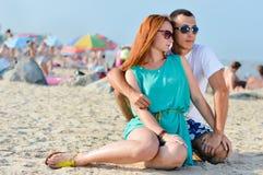 Unga lyckliga par tillsammans på att omfamna för sandig strand Royaltyfria Foton