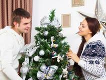 Unga lyckliga par vid det Cristmas trädet Arkivbild