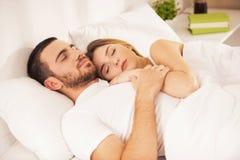 Unga lyckliga parlögner i vit säng och sömn Royaltyfri Fotografi