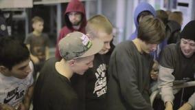 Unga lyckliga pojketagandecans med energi dricker från packen folk Konkurrens i skatepark arkivfilmer