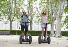 Unga lyckliga turist- par som rider den segway tyckande om staden, turnerar i Madrid parkerar i Spanien tillsammans Royaltyfri Foto