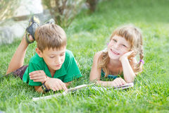 unga lyckliga ungar, barnläseböcker på naturlig backgrou Royaltyfri Bild