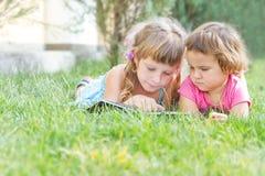 unga lyckliga ungar, barnläseböcker på naturlig backgrou Royaltyfri Foto