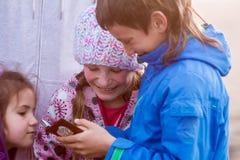 Unga lyckliga ungar, pojke och flickor som ler på och ser smth Royaltyfri Bild