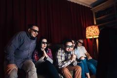 Unga lyckliga vänner i exponeringsglas 3d håller ögonen på tv hemma fotografering för bildbyråer