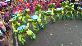 Unga män i utsmyckad kokosnötdräkt dansar längs gatan, en festival för att hedra en skyddshelgon