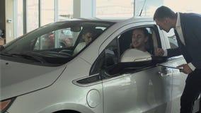 Unga män kontrollerar en modern bil och talar med chefen i bilåterförsäljare stock video