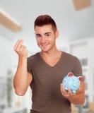 Unga män med en blå moneybox Arkivbild