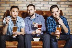 Unga män med ett öl som håller ögonen på matchen på TV royaltyfri bild