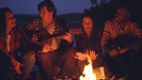 Unga män och kvinnor är sjungande sånger till gitarren som vilar runt om lägereld och tycker om på musik- och godaföretaget lager videofilmer