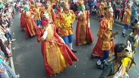Unga män och kvinnor i medeltida dräkt dansar längs gatan, en festival för att hedra en skyddshelgon