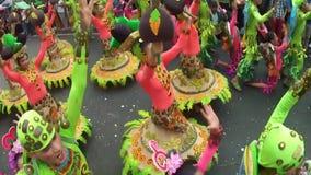 Unga män och kvinnor i utsmyckad kokosnötdräkt dansar längs gatan, en festival för att hedra en skyddshelgon
