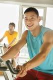 Unga män på stationära cyklar som övar i idrottshallen royaltyfria foton