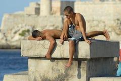 Unga män solbadar på den Malecon skyddsmuren mot havet i havannacigarren, Kuba Royaltyfria Bilder
