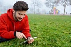 Unga män som använder den digitala minnestavlan parkerar offentligt arkivfoton