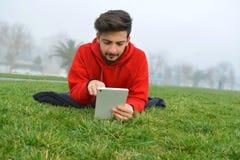 Unga män som använder den digitala minnestavlan parkerar offentligt royaltyfri bild