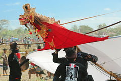 Unga män som förbereder sig att lansera en enorm drake med ett drakehuvud Arkivfoto