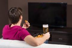 Unga män som håller ögonen på TV. Bakre sikt av unga män som dricker öl och royaltyfri fotografi