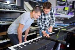 Unga män som ser tangentbord i musikal, shoppar arkivbilder