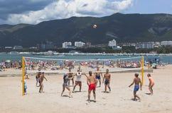 Unga män som spelar volleyboll på den sandiga stranden av semesterorten Gelendzhik, Krasnodar region Royaltyfri Bild
