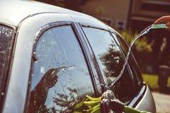 Unga män som tvättar silverbilen med pressat vatten och borsten på den soliga dagen Stäng sig upp av lokalvårdbilen på sommartid Fotografering för Bildbyråer