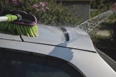 Unga män som tvättar silverbilen med pressat vatten och borsten på den soliga dagen Stäng sig upp av lokalvårdbilen på sommartid Arkivfoton