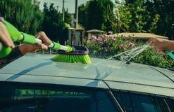 Unga män som tvättar silverbilen med pressat vatten och borsten på den soliga dagen Stäng sig upp av lokalvårdbilen på sommartid Royaltyfria Bilder