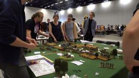 Unga män spelar tabellden miniatyrmilitära roll-spela leken lager videofilmer