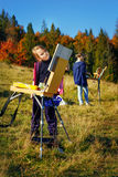 Unga målare på arbete nära vattenfallet Arkivfoton