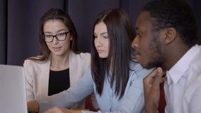 Unga mång- etniska afrikansk amerikankollegor kvinna och man som talar, medan sitta på skrivbordet med bärbara datorn i modernt k arkivfilmer