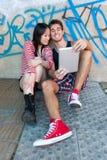Unga mång--person som tillhör en etnisk minoritet par genom att använda en minnestavlaPC Arkivfoto
