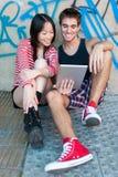 Unga mång--person som tillhör en etnisk minoritet par genom att använda en minnestavlaPC Royaltyfria Bilder