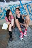 Unga mång--person som tillhör en etnisk minoritet par som läser en bok Royaltyfria Bilder