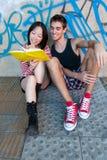 Unga mång--person som tillhör en etnisk minoritet par som läser en bok Royaltyfri Fotografi