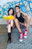 Unga mång--person som tillhör en etnisk minoritet par som läser en bok Arkivfoton