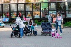 Unga mammaflickor med sittvagnar och småbarn går i en stad parkerar mot en bakgrund av gröna träd arkivfoton