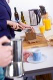 Barn bemannar och den lyckliga kvinnan som förbereder frukosten i deras kök Arkivfoto