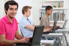 Unga manar som är funktionsdugliga på datorer Fotografering för Bildbyråer
