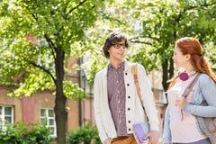 Unga manliga och kvinnliga högskolestudenter som talar, medan gå på gatan arkivbild