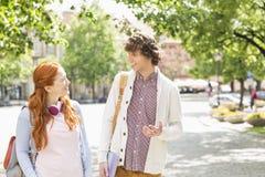 Unga manliga och kvinnliga högskolestudenter som talar, medan gå på vandringsledet royaltyfri bild