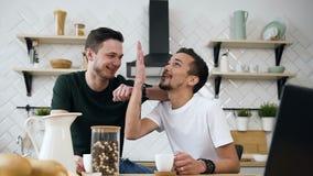 Unga manliga par sitter på köksbordet som talar något som är rolig, medan dricka kaffe i morgonen på kök stock video