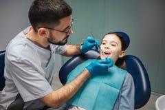Unga manliga tandläkarekontrollflickas tänder Hon håller munnen öppnad Tand- hjälpmedel för manbruk Flickan sitter i stol i rum arkivbilder