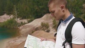 Unga manliga turist- ställningar på steniga kullar nära bevattnar yttersida av sjön i berg som kontrollerar hans väg med den papp lager videofilmer