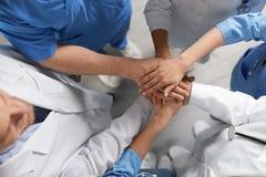 Unga medicinska doktorer som tillsammans sätter händer inomhus silhouettes det bl?a begreppsfolket f?r bakgrund skyenhet arkivfoton