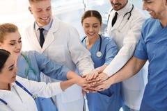 Unga medicinska doktorer som tillsammans sätter händer silhouettes det bl?a begreppsfolket f?r bakgrund skyenhet royaltyfri foto